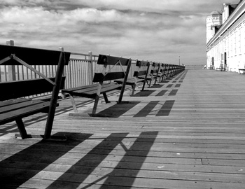 Series of benches on a beach boardwalk.