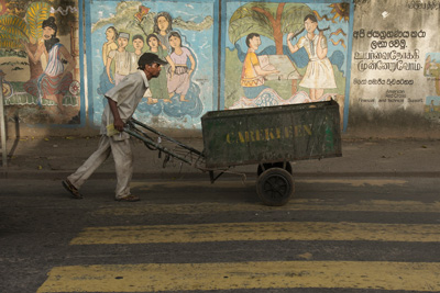 A Colombian street cleaner pushes his cart past a storyboard