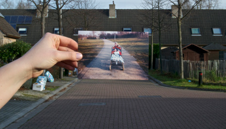 Hand holding up photo in front of street