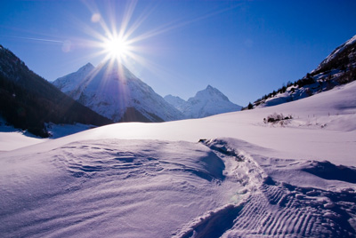 Snowy mountains with a sunburst at the top
