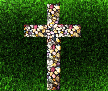 Cross made of pebbles on green lawn