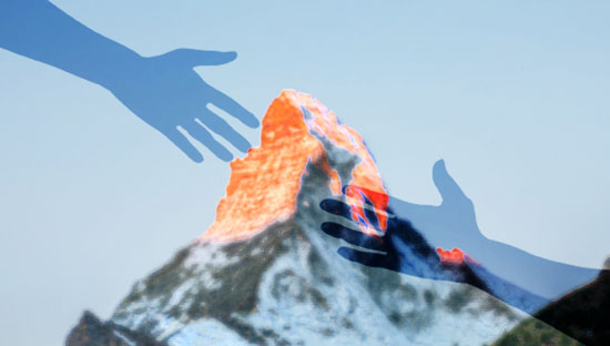 Two hands reaching for each other in front of the Matterhorn mountain