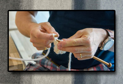 Man's hands knitting, with background of lopi wool blanket