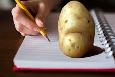 Potato on notebook with hand writing in pencil