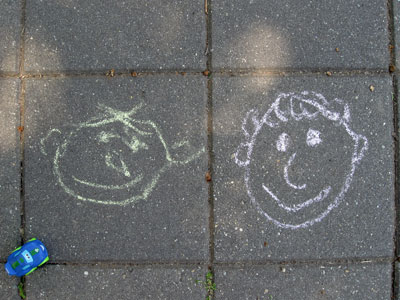 Two chalk faces on a sidewalk