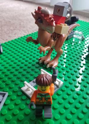 LEGO minifig running from dinosaur