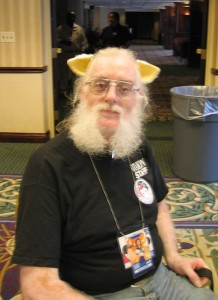 A man in a black T-shirt, wearing wolf ears, and with a full set of gray muttonchops, sits on a chair, looking at the camera